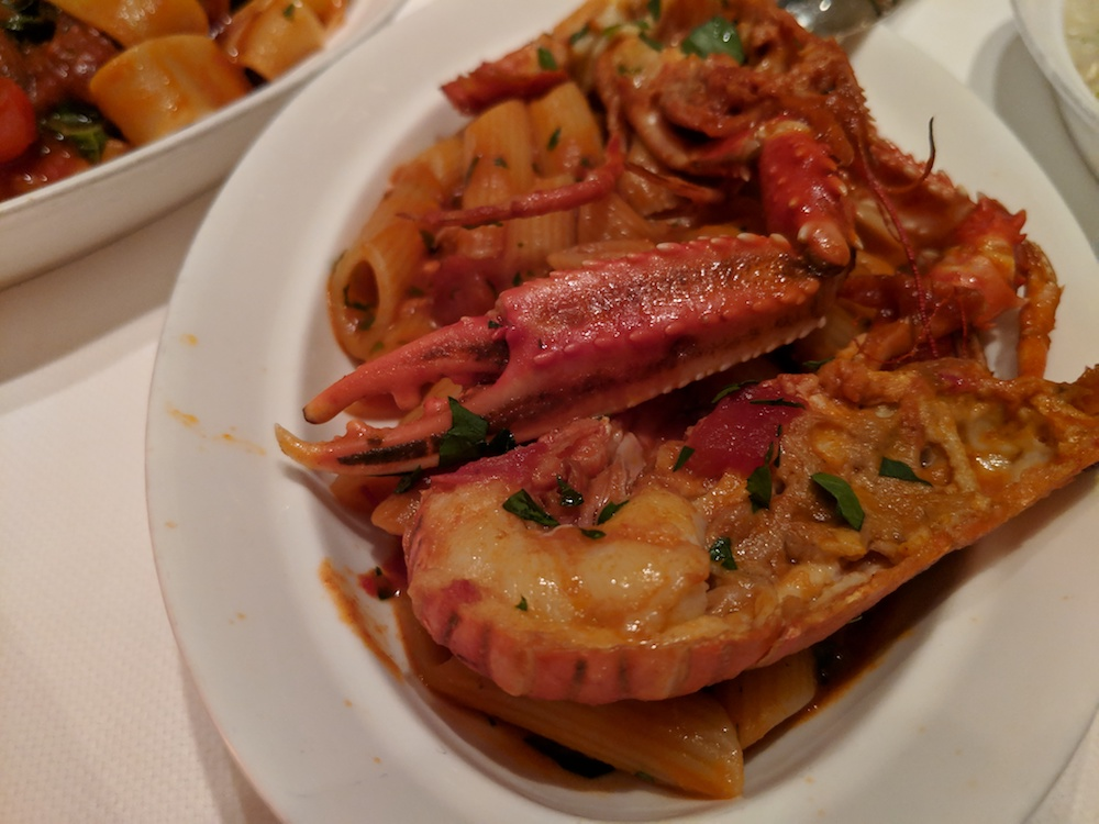 Seafood feast assembled on the plate - lobster with pasta and San Marzano sauce